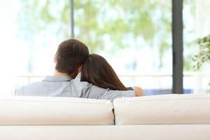 Ehepaar sitzt zufrieden uns sicher auf dem Sofa