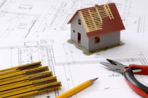 Neubaufinanzierung / Altbaufinanzierung - Hausmodell auf Planungszeichnungen