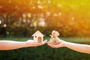 2 Hände halten Neubau und Geld (kosten) in Waage